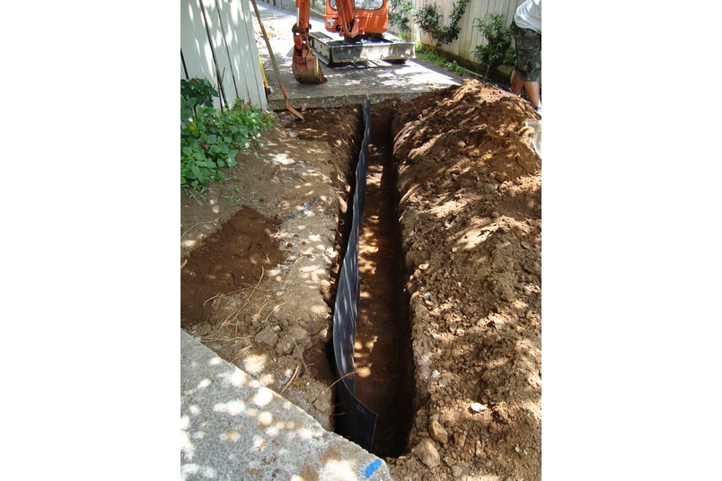 Installation of root barrier, to isolate tree roots from underground services or paving