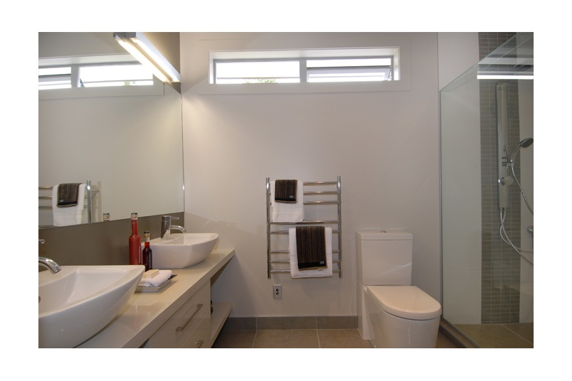 Narrow awning windows provide natural light and ventilation into bathroom areas
