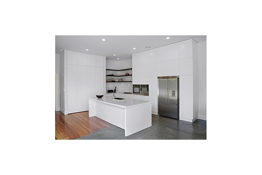 Mt Eden Kitchen – sleek white cabinetry and a stud height of 3.6m conceals a wealth of storage space
