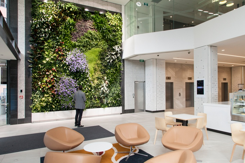 A large green wall in a large atrium.